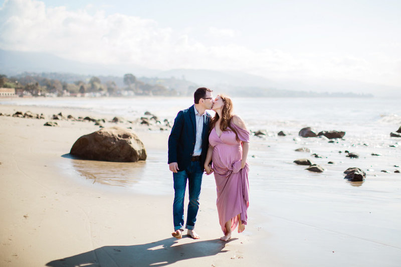 A couple walks along the beach and kisses during their maternity session in Montecito