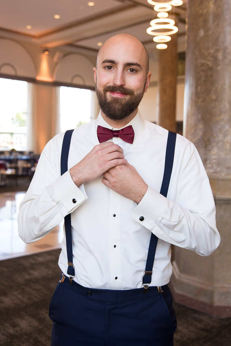 groom tying bowtie on wedding day in lobby of cityflats ballroom port huron