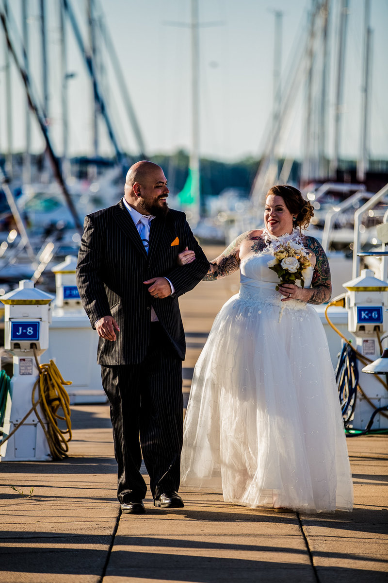 Bride and groom walk arm in arm along the dock at the Erie Yacht Club