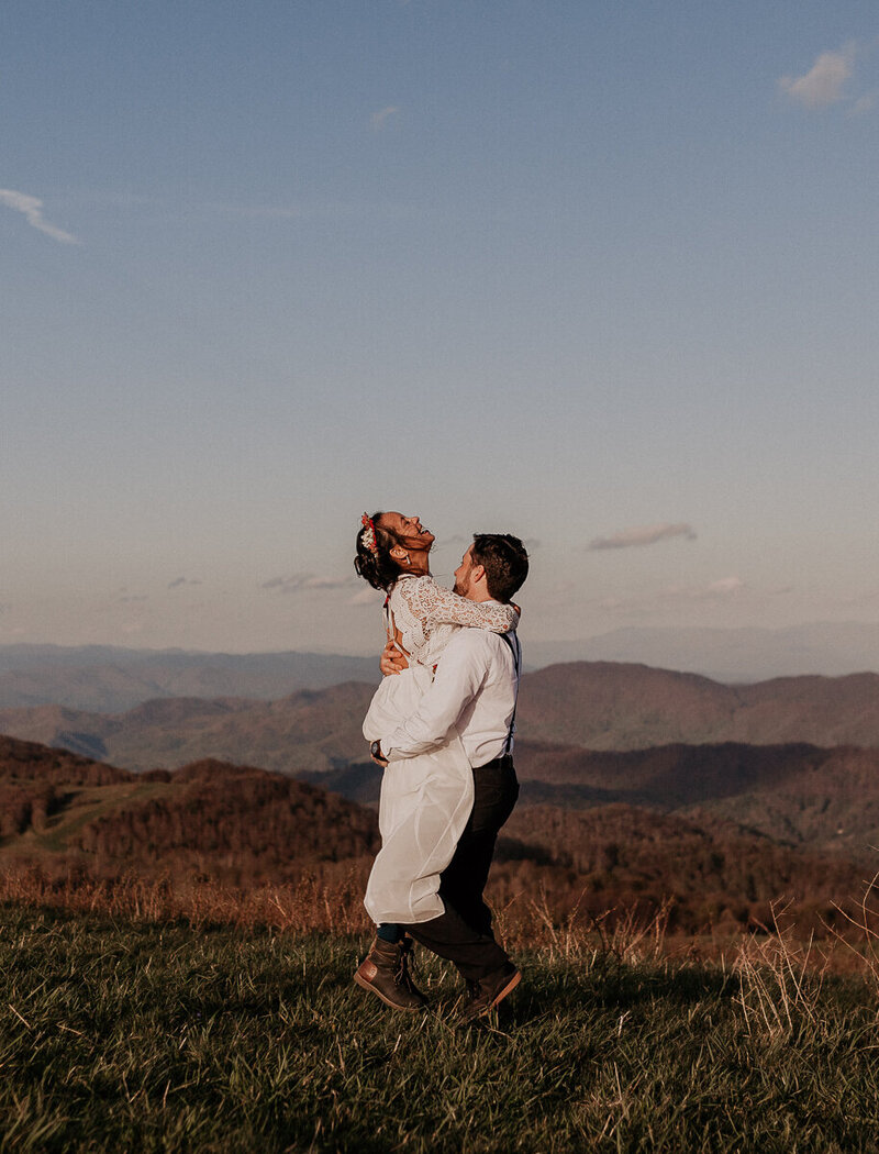 Couple laughing and embracing during their wedding day in Asheville, NC.