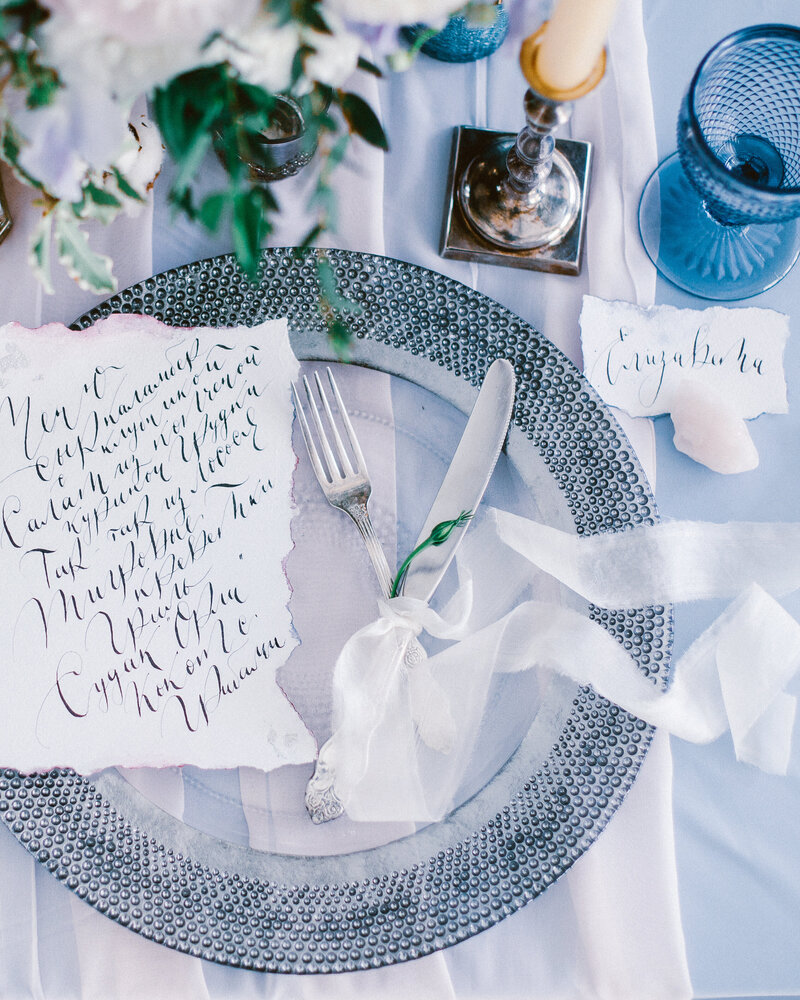 Beautiful wedding calligraphy cards sit atop a silver charger  plate with cutlery on luxury wedding table.