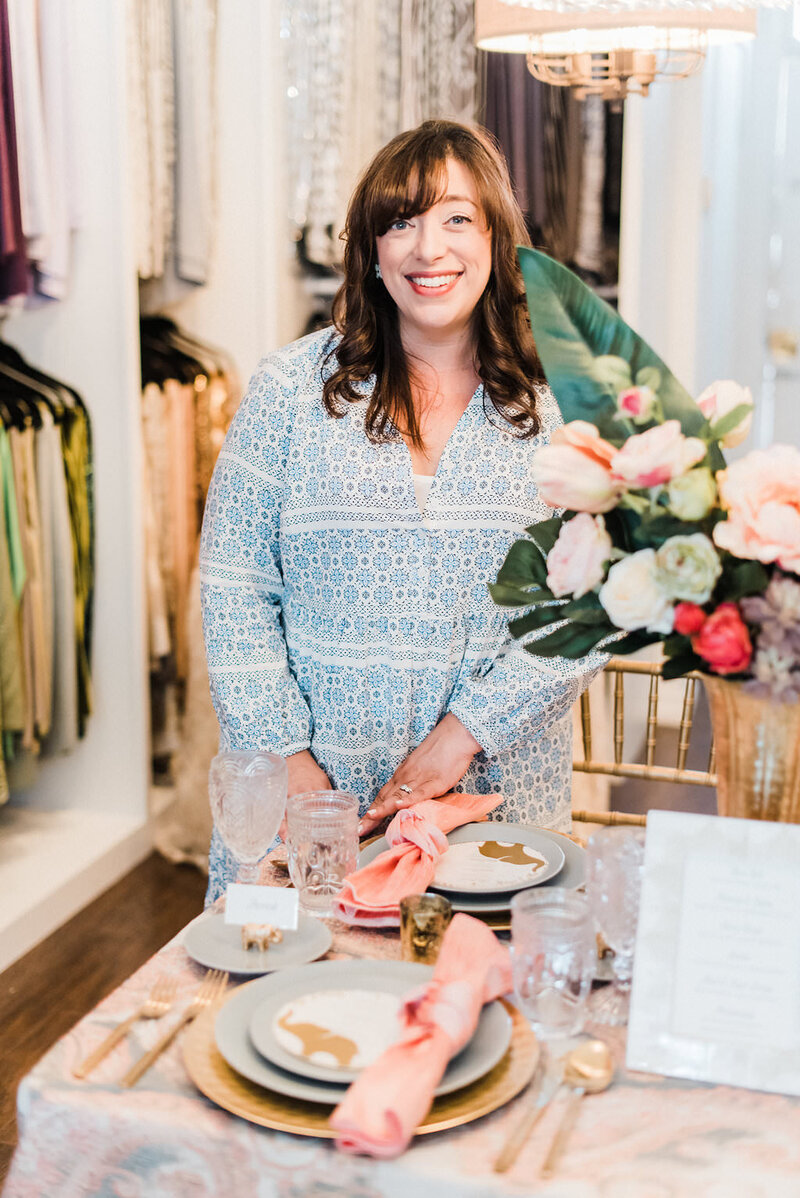 Moxie Bright Events founder, Renee Dalo, smiles while arranging a wedding tablescape