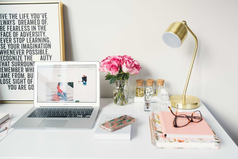 A desktop with an open laptop, a mason jar with fresh pink roses, a few stacked notebooks, a phone faced down, pair of glasses, a few office supplies in glass jars with cork lids, and a gold gooseneck lamp.
