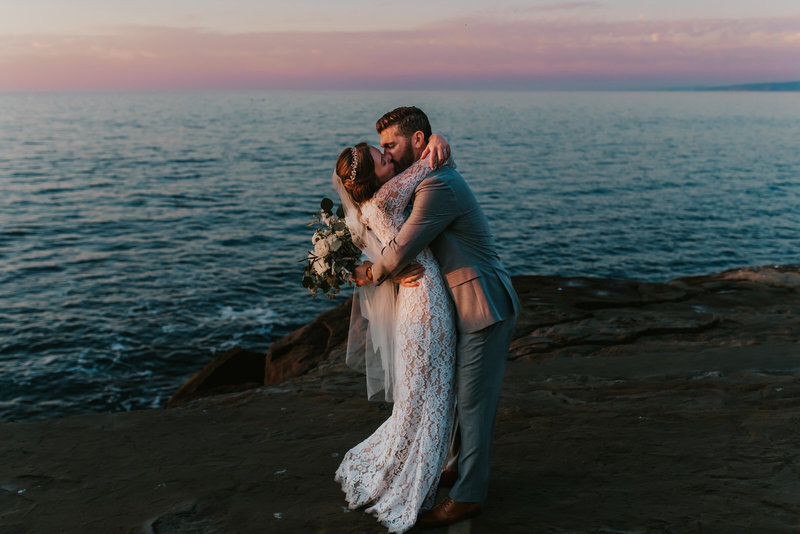 bride and groom kissing on sunset cliffs