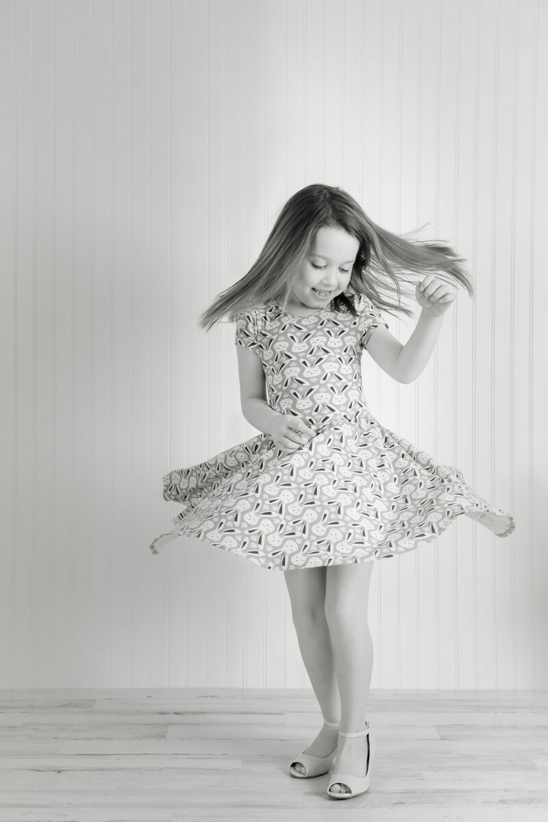Studio portrait of a young girl spinning in her flowing dress.