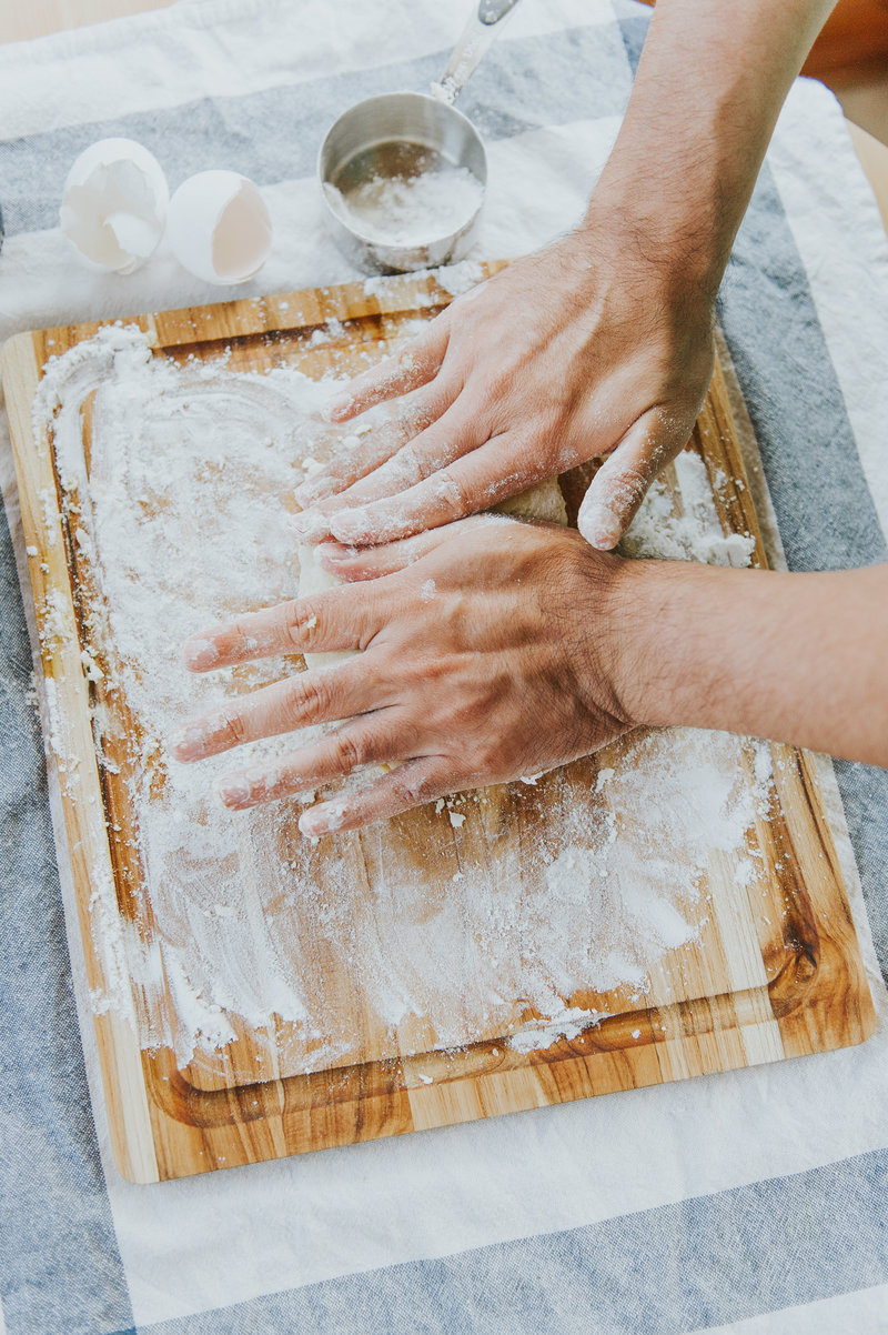 Hands knead dough into pasta dough
