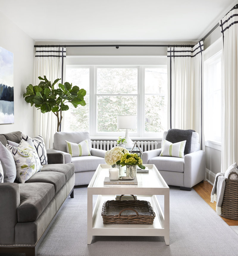 Living room with dark grey sofa and light grey armchairs in Etobicoke home