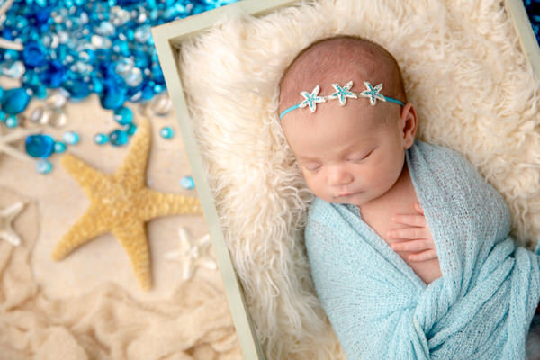 Newborn girl swaddled in blue on a beach themed set with starfish