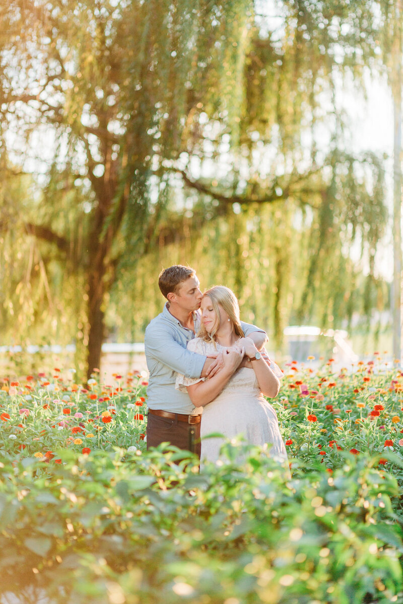 Engaged couple poses in flower field near Indianapolis Canal