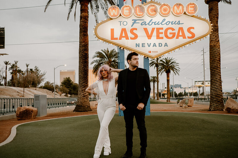 Man and women standing in front of the fabulous Las Vegas Sign