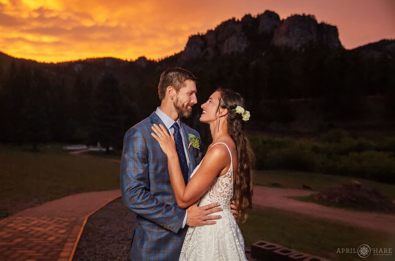 Gorgeous orange sunset sky on a summer wedding day at Mountain View Ranch in Pine