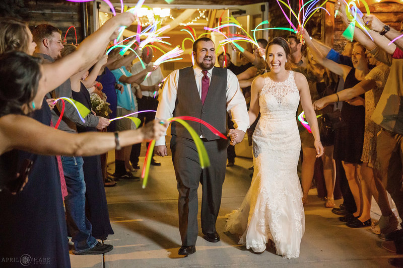 Couple exits their wedding reception with glow sticks at Church Ranch Event Center
