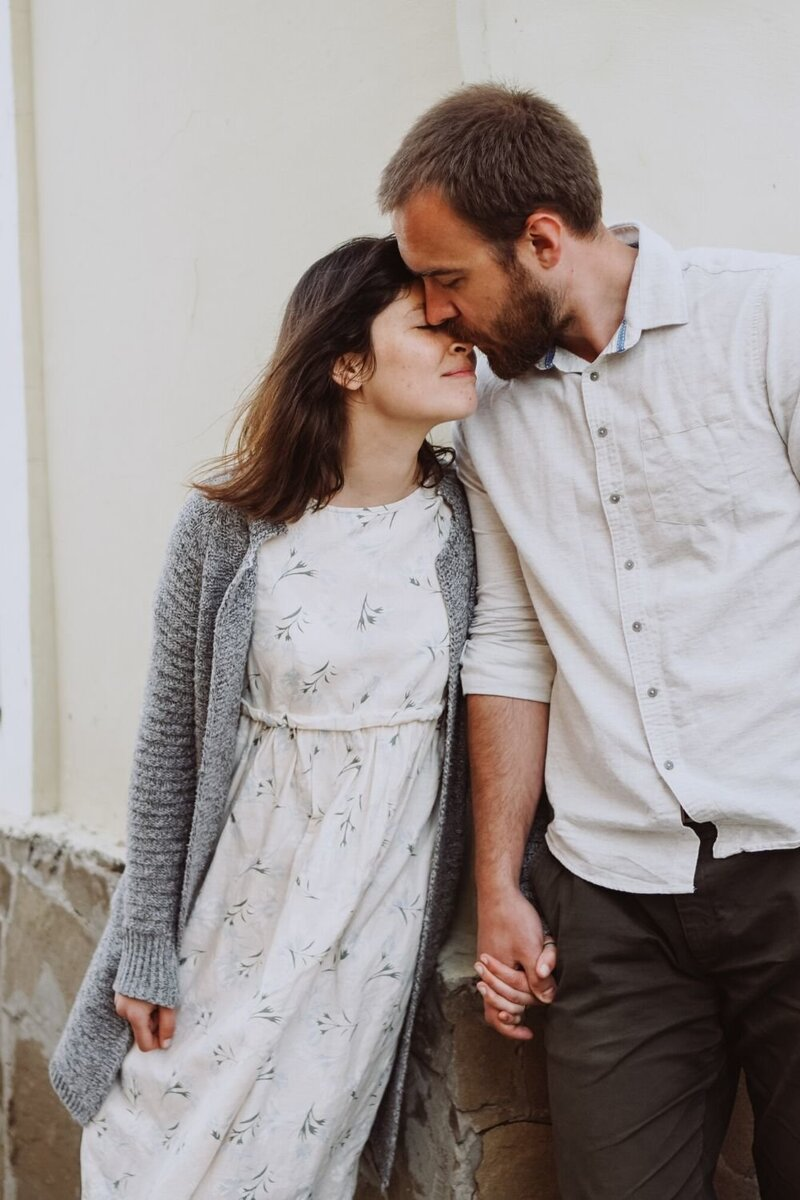 A man kisses his wife on the nose as both hold hands next to a blank wall. This could symbolize the strong bond that is created as a result of couples communication therapy in Florida. Contact Idit Sharoni for
