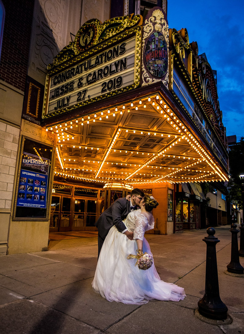 Bride and groom kiss under the lighted marquee of the Warner Theatre