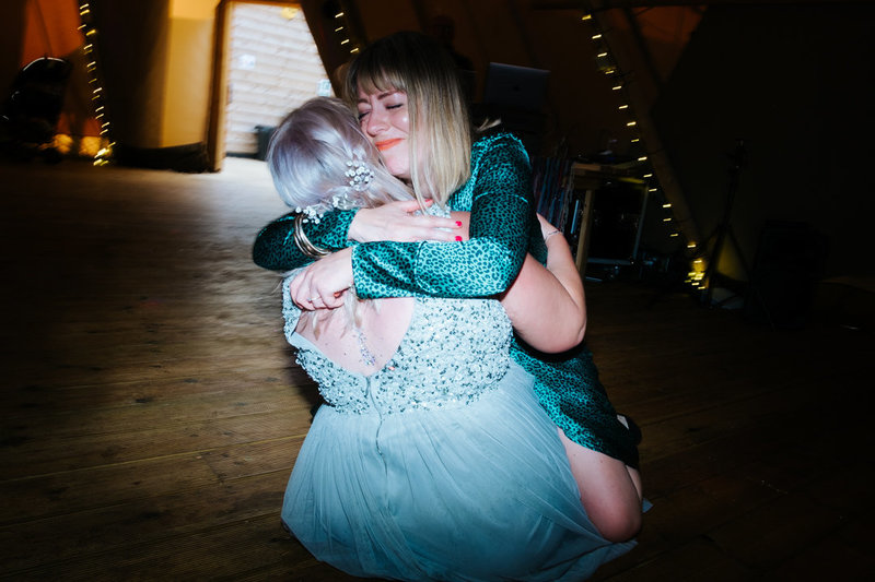 bridesmaid and friend sit hugging on the Tipi  dance floor at their hadsham farm wedding