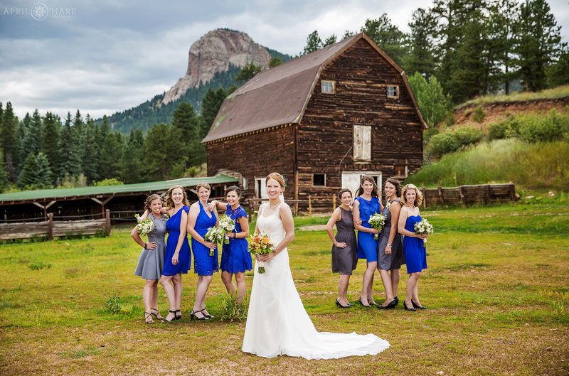 Bride with Bridesmaids wearing bright blue in front of barn at Mountain View Ranch