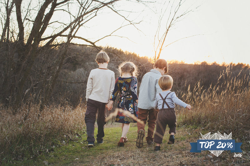 Four siblings walking on a trail through the Iowa prairie