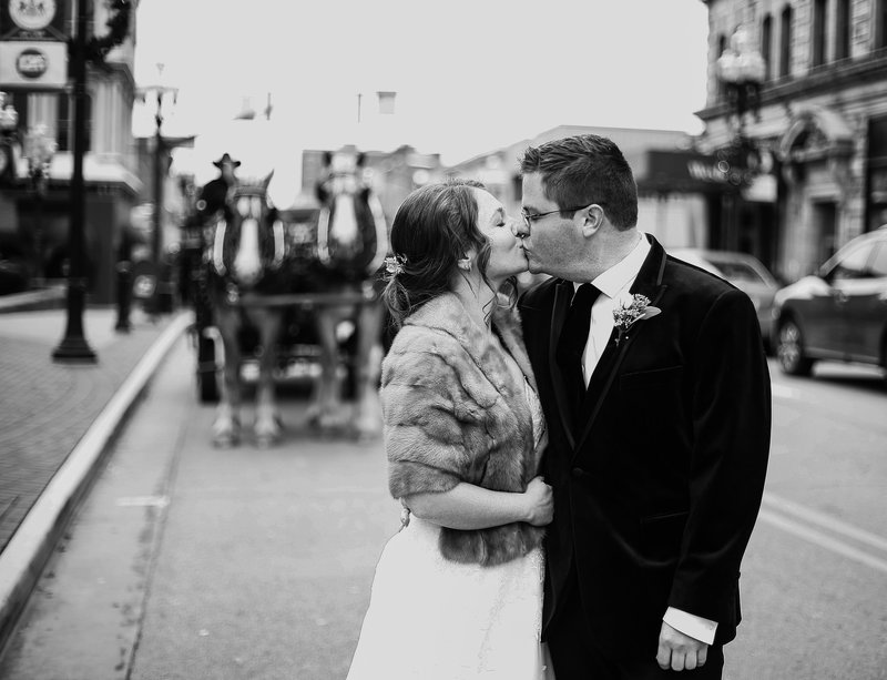 Bride and groom kiss in the street with horse drawn carriage in the background
