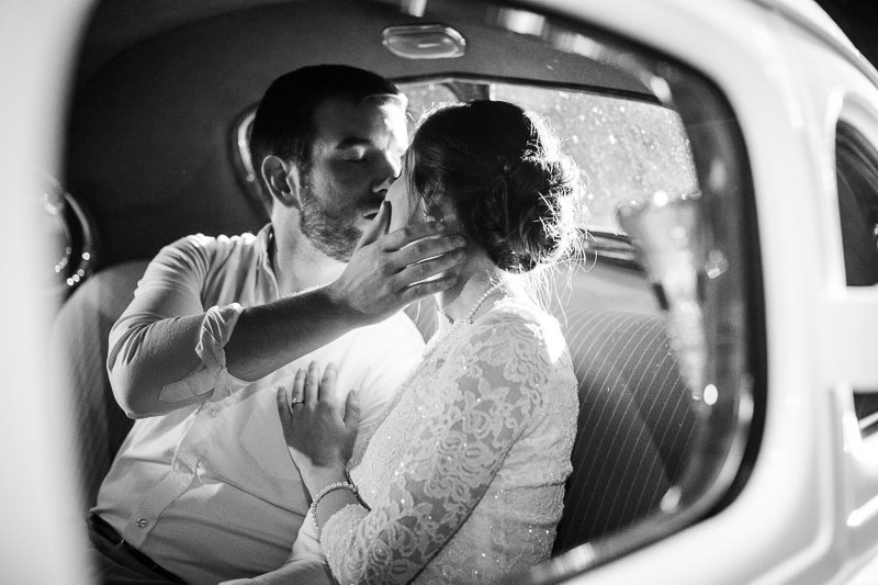 Classic black and white image of bride and groom in get-away car.