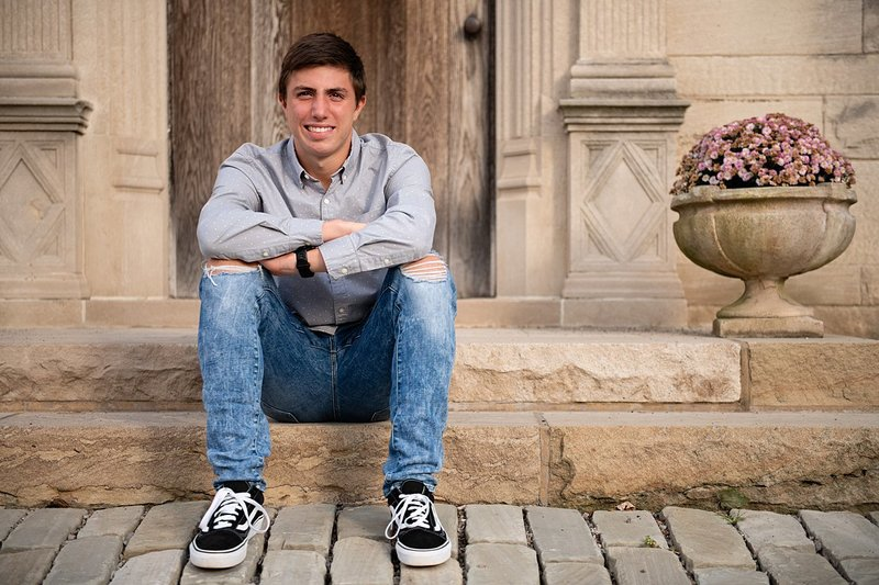 High school senior boy seated in front of brown door with Mums at Hartwood Acres in Pittsburgh, PA