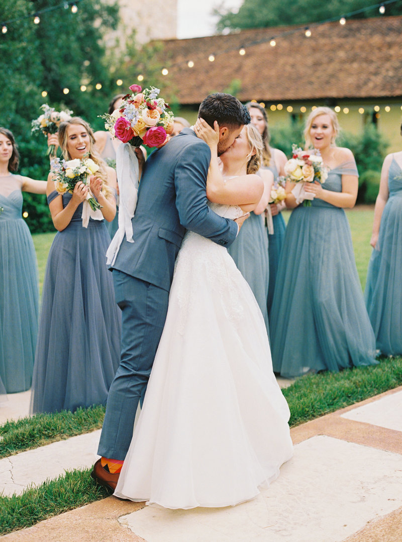 Groom and bride kisses with bridesmaids cheering