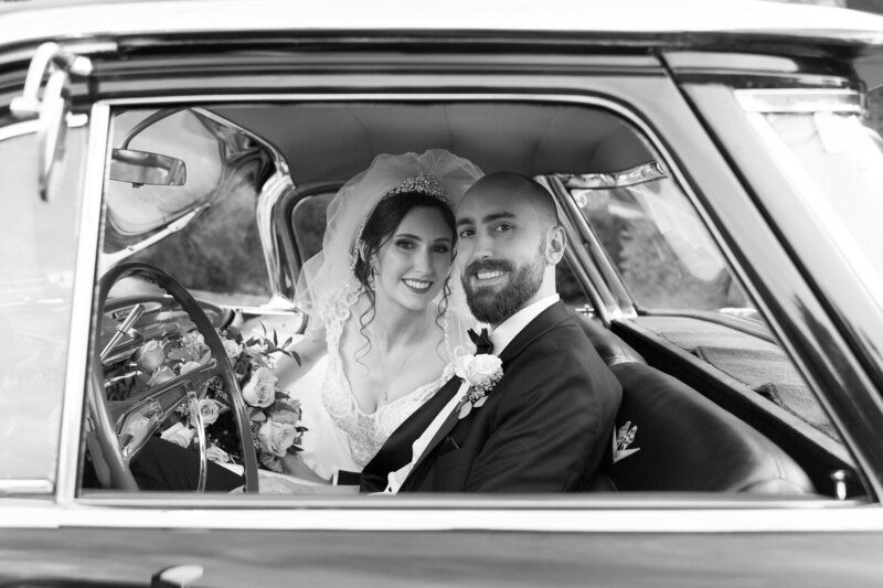 bride and groom inside of vintage car on wedding day in detroit michigan