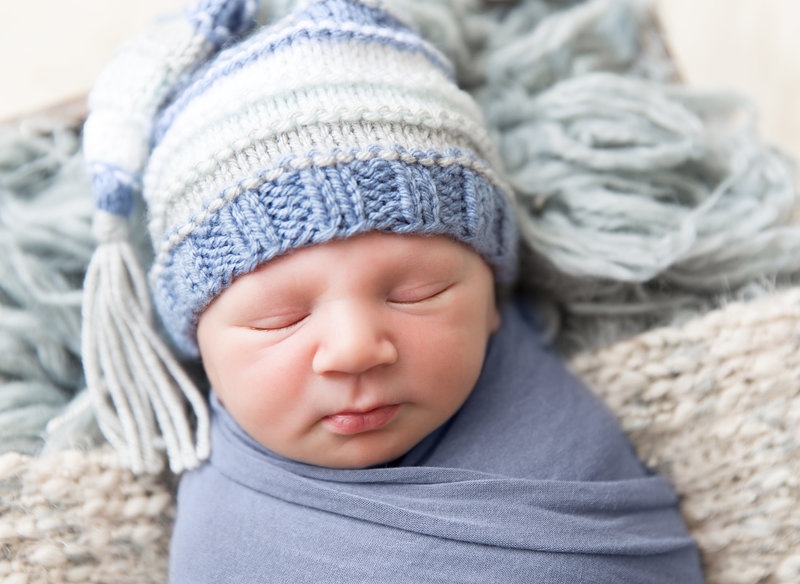 baby boy with blue and white tassel hat
