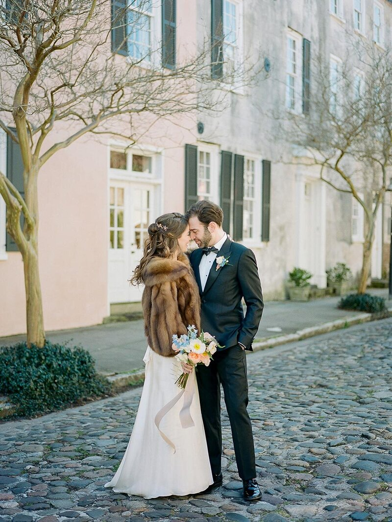 Husband and wife in their wedding day outfits look into each others eye on Charleston's cobblestone streets