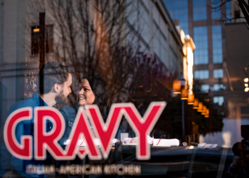 Couple sits at a table inside the window for Gravy, a restaurant in Downtown Raleigh