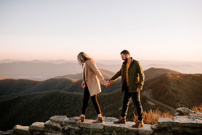 man and woman holding hands while walking with mountains in background