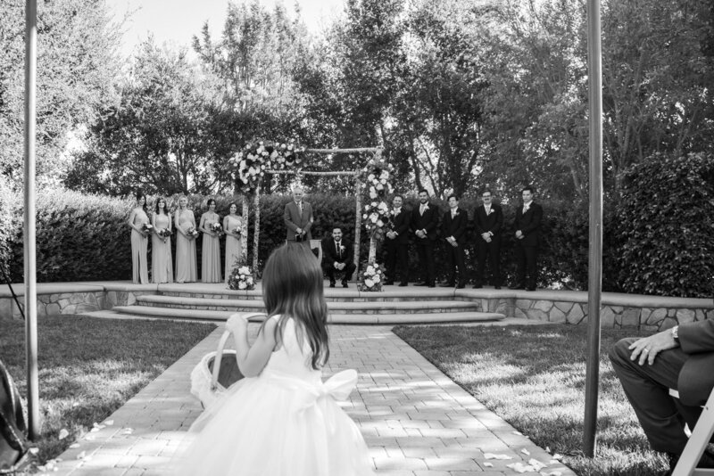 Black and white image of a flower girl walking down the aisle