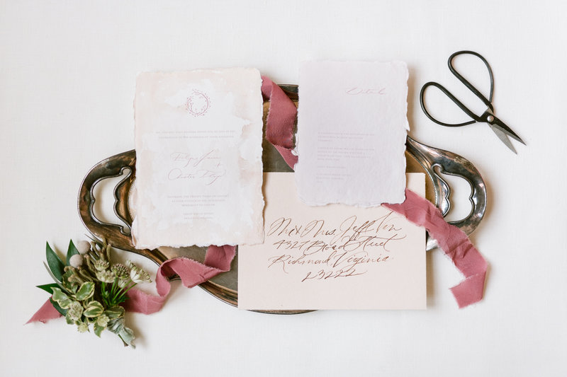 Elegant invitation suite with beautiful script laying on a brass platter with mauve ribbon.