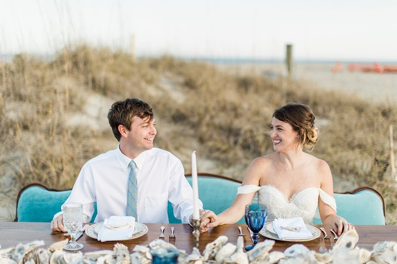 A bride and groom sit down to eat at a styled table in the sand dunes.
