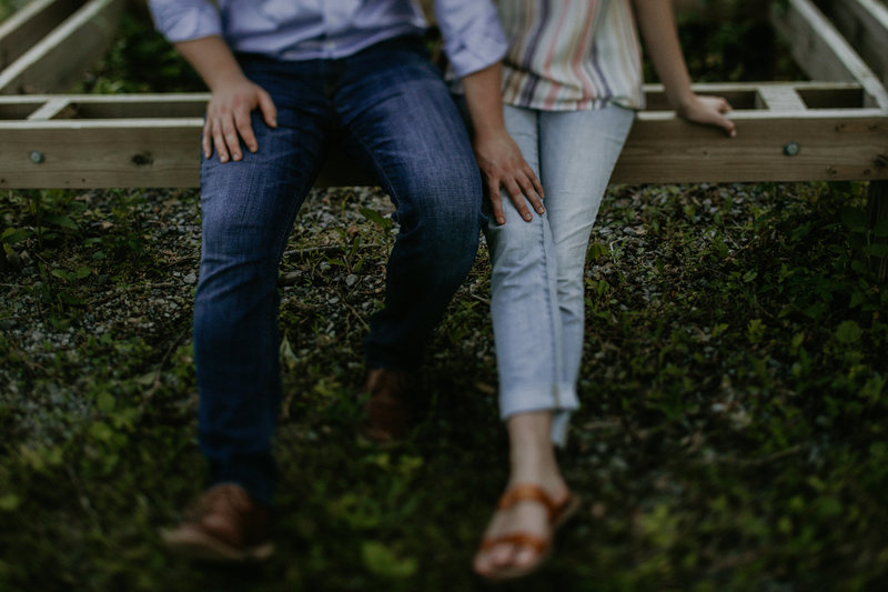 A man's hand on a woman's leg during an engagement session.