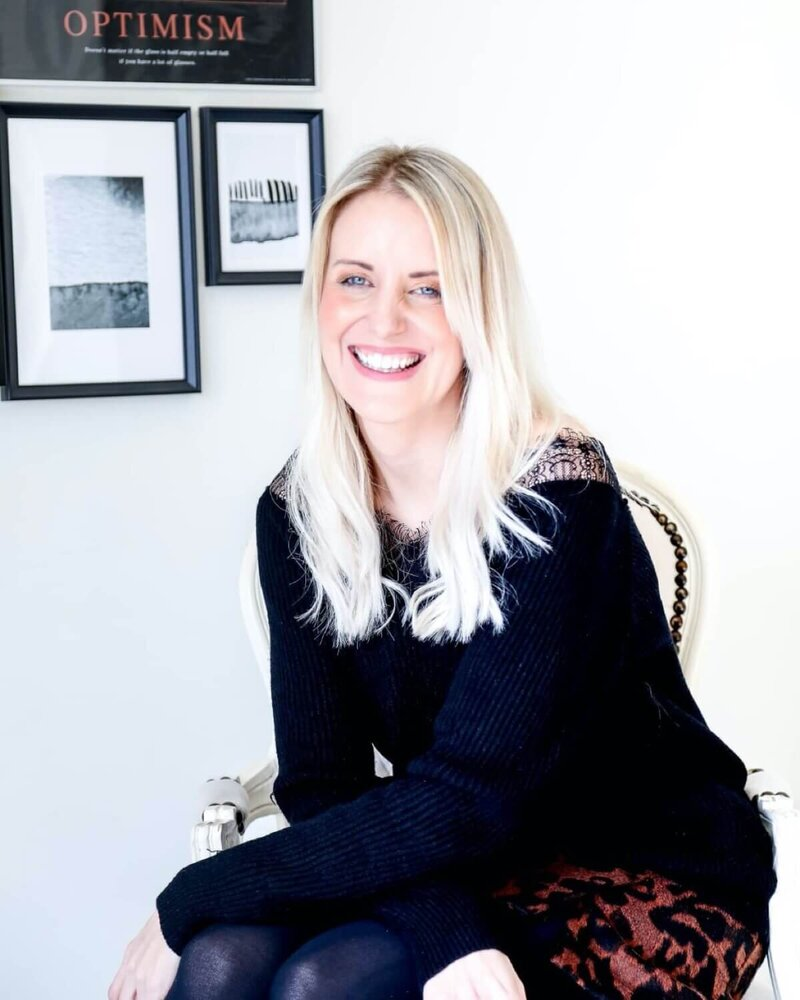 Natalie Kerr sitting on a chair in front of a wall with pictures hung on it