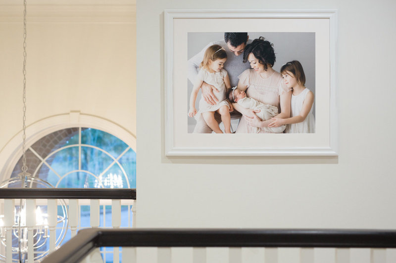 large framed picture of family with a newborn