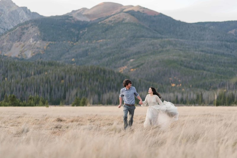 Samantha Schaub, Texas elopement photographer captures mountain couple running in field at rmnp after their elopement