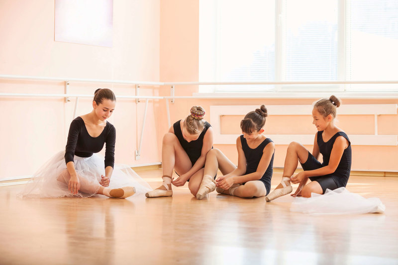 photodune-20305787-young-ballerinas-putting-on-pointe-shoes-while-sitting-on-floor-in-ballet-class-l