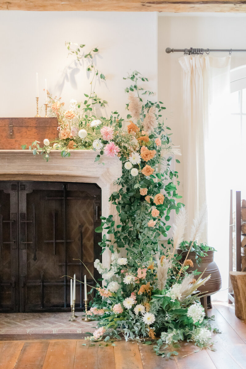 floral covered fireplace mantle at French Inspired Private Estate wedding in charlottesville virginia by costola photography