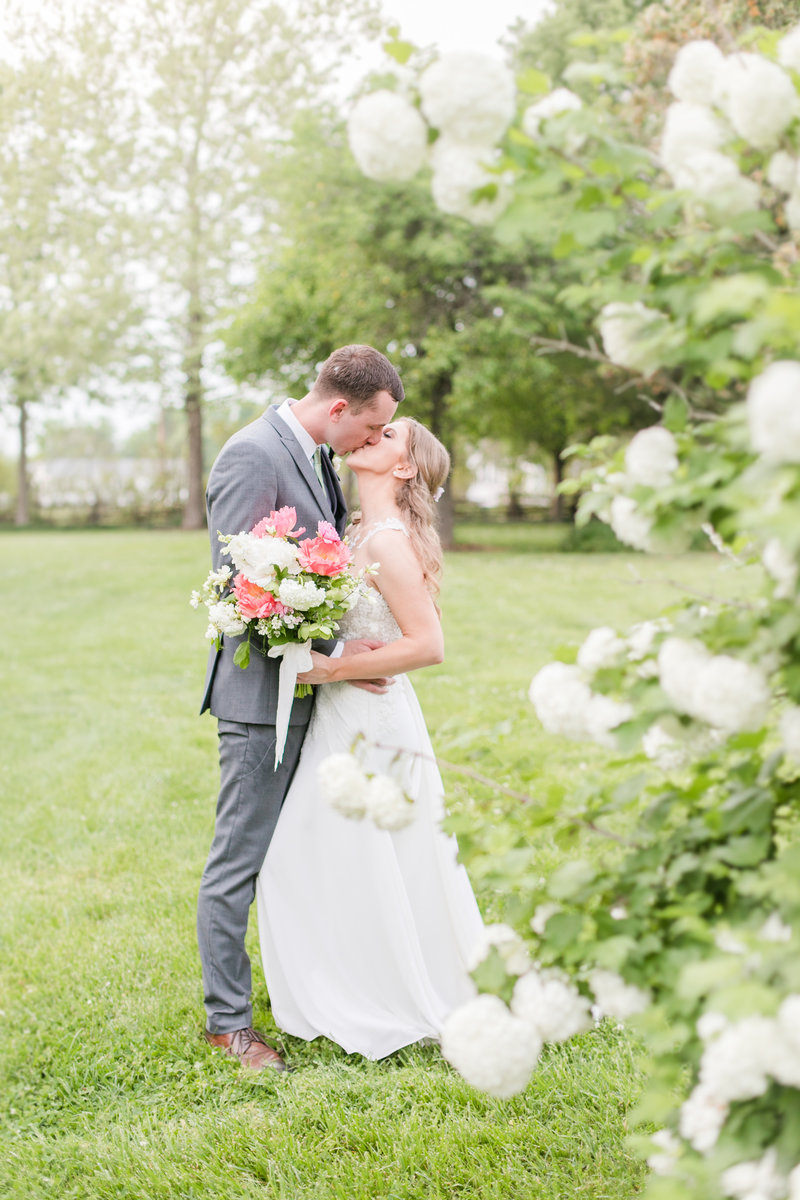 bride and groom kissing beside flowers at Maryland venue Ocean Hall by Costola Photography