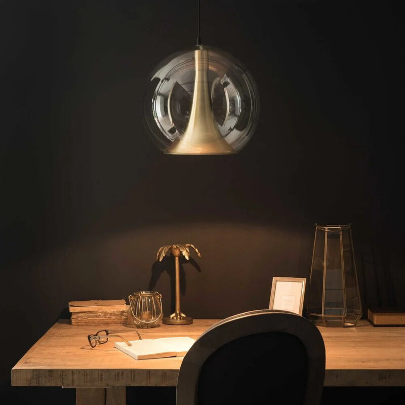 A glass and gold modern pendant is pictured above a black home office desk area.