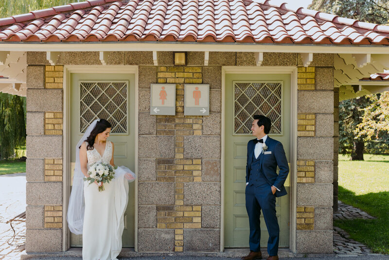 bride and groom standing in front of outdoor bathroom signs  in Ottawa
