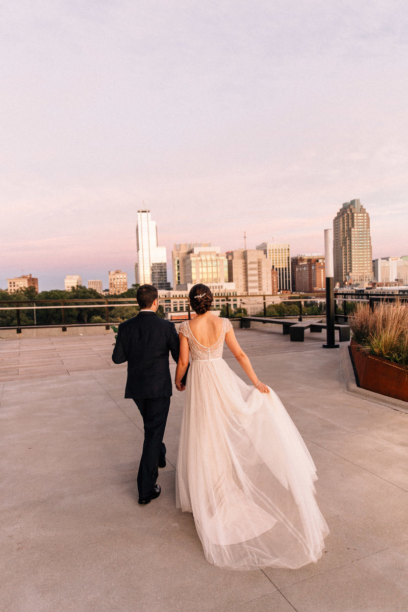 bride looks over downtown raleigh at the Dillon  rooftop