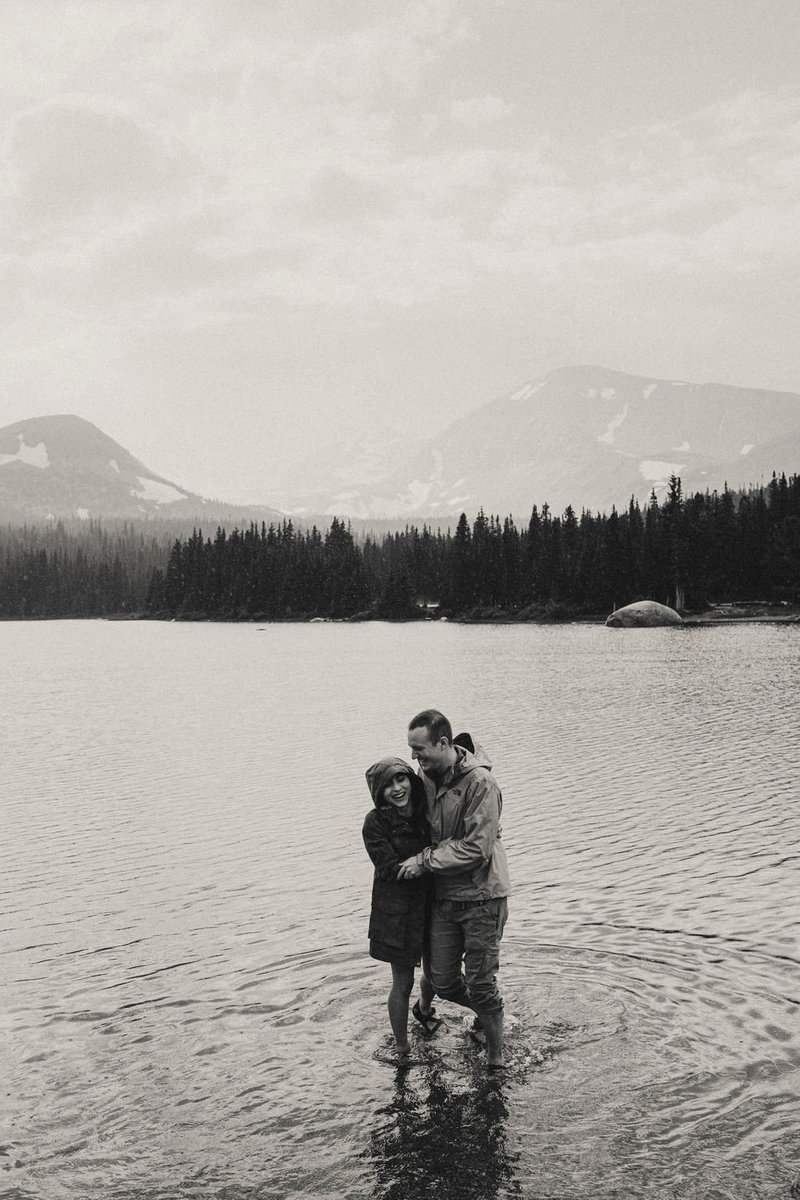 Mike and Mandi stand ank;e-deep in a lake in the mountains and look at the camera and each other, laughing.