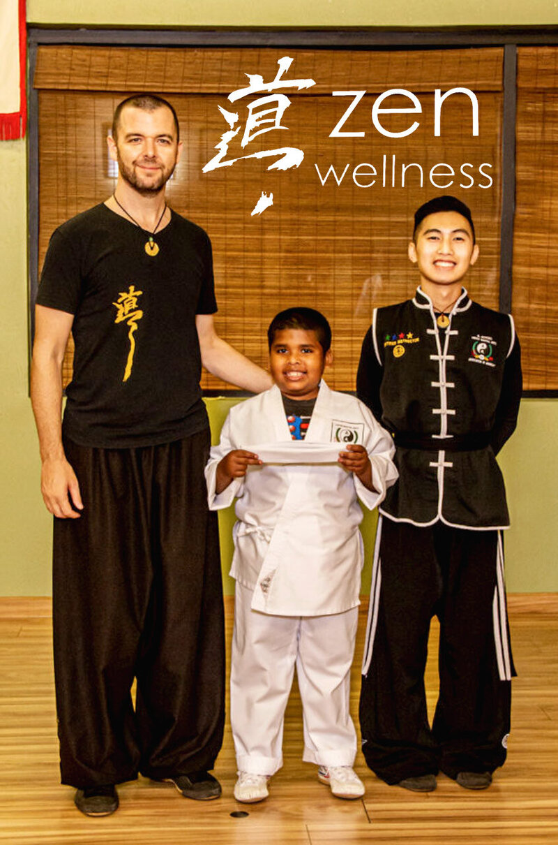 Instructors Jason Campbell and Allen standing on either side of young student holding belt and wearing gi while smiling