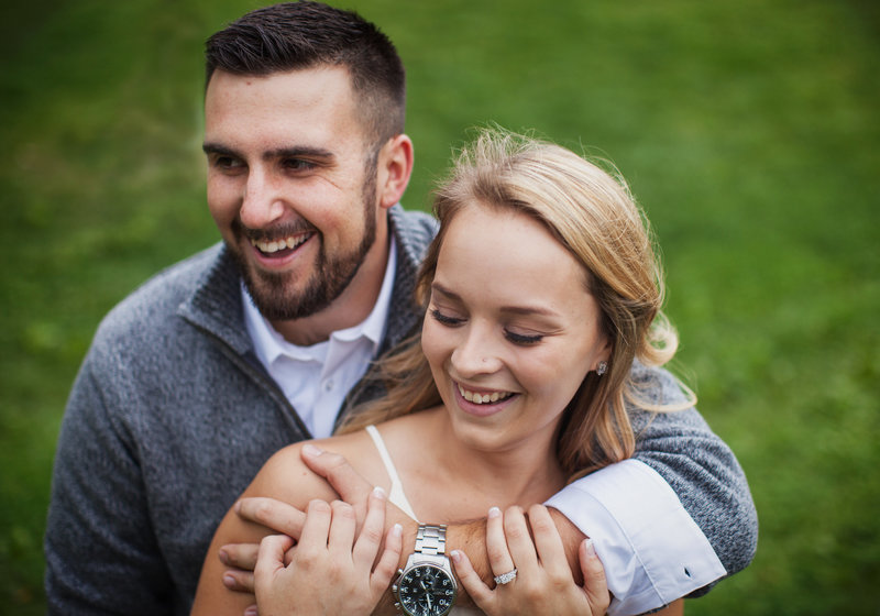 Engaged couple hugging and smiling on grassy lawn.