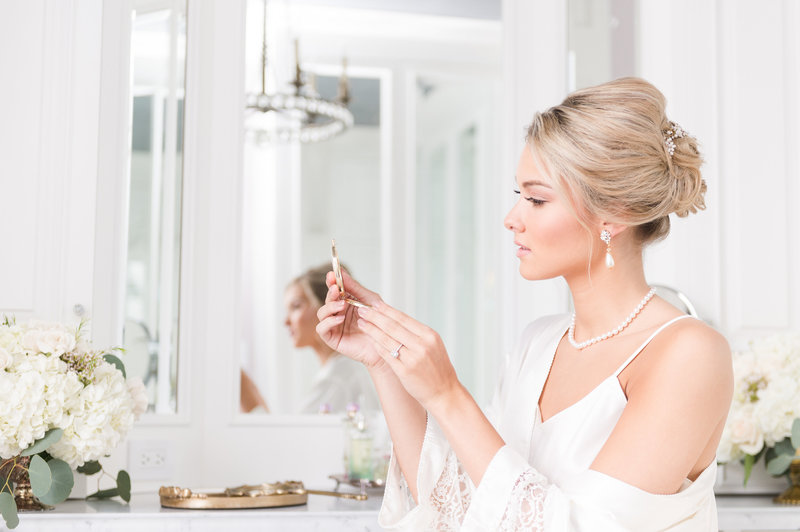 Beautiful bride looks at herself in the mirror