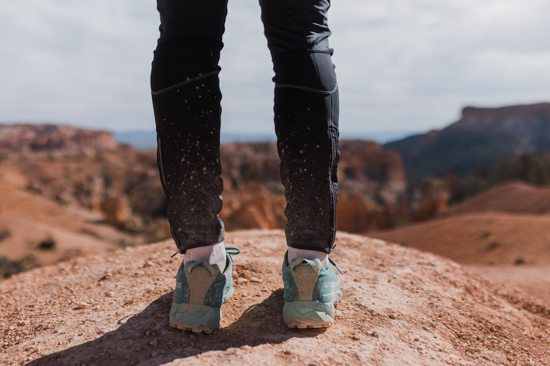 picture of woman's legs wearing pants and tennis shoes standing on  a rock
