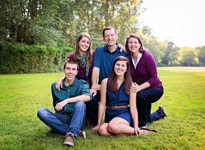 Family gathers for portrait on grassy field