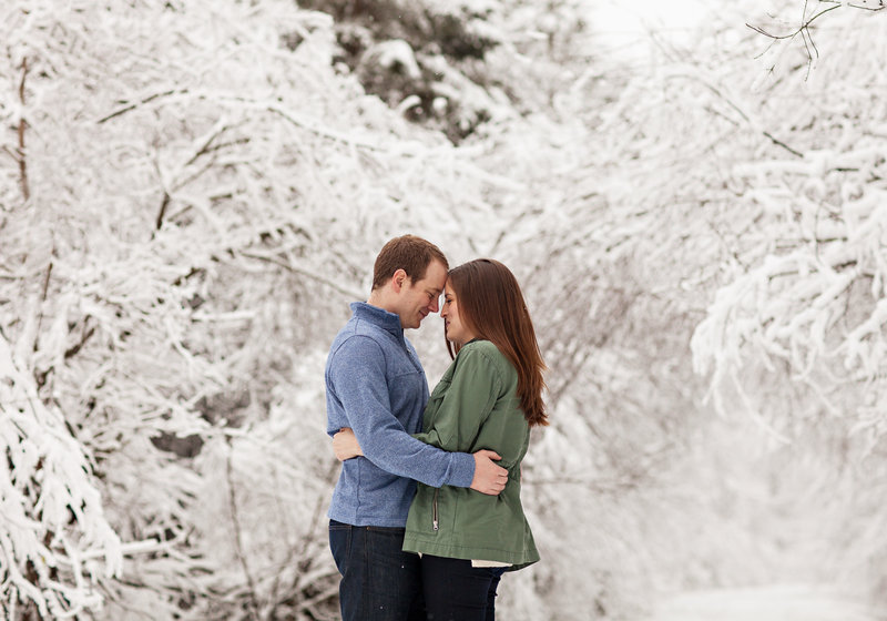 Engaged couple are embracing.  Trees behind them are thick with snow.